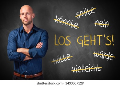 "businessman standing in front of a chalkboard with stroked words like could and should and ""Let's go"" in German"