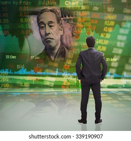 Businessman standing in front of concept of Japanese 10000 YEN on stock market ticker