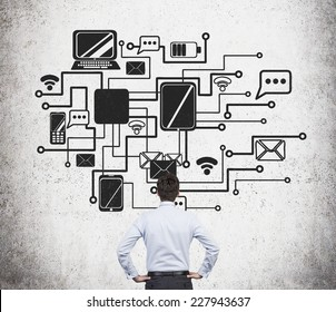 Businessman is standing in front of the flow chart of a corporate internal network.