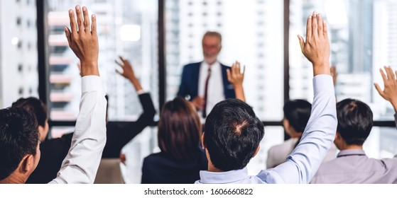 Businessman standing in front of group of people in consulting meeting conference seminar and showing hand to answer question at hall or seminar room.presentation and coaching concept
