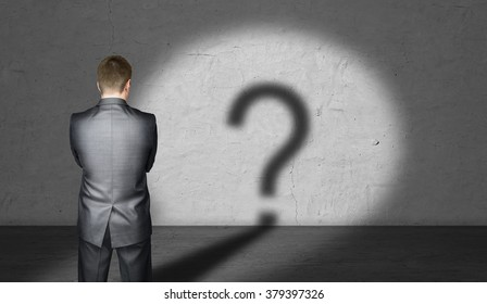 Businessman standing in front of a lit wall with question mark looking like shadow