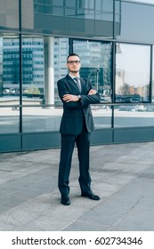 Businessman standing in front of office by day