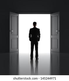 businessman standing in front of opened doors