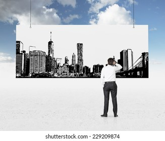 Businessman is standing in front of the picture of the city.