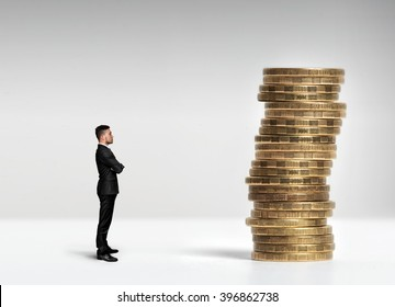 Businessman standing in front of a stack scale rouble coins