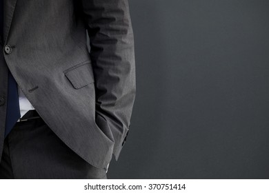 Businessman standing with hand in pocket against grey background