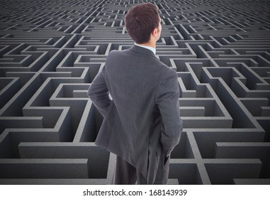 Businessman standing with hands on hips against difficult maze puzzle