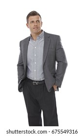Businessman standing with hands in pockets, looking away.