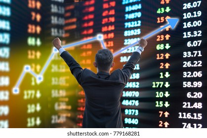 Businessman standing happy expression at stock market chart, Financial data on electronic board