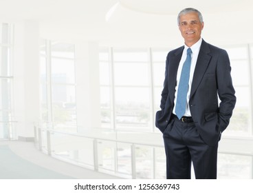 Businessman standing in high key office setting with his hands in pockets.