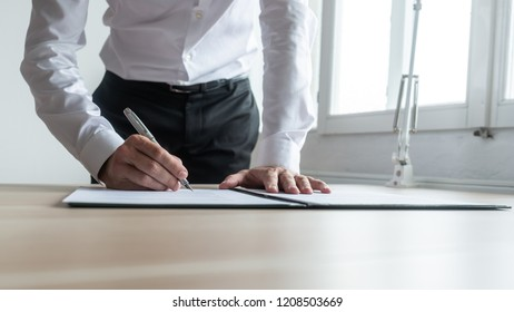 Businessman standing at his desk leaning to sign legal document or paperwork with fountain pen.