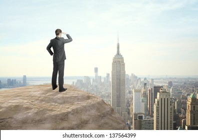 businessman standing and looking at city in distance