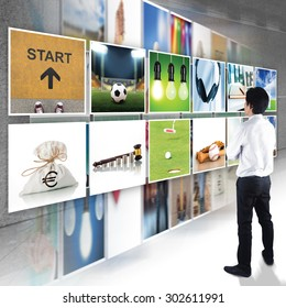 Businessman standing looking at Digital photo gallery images streaming, TV screen