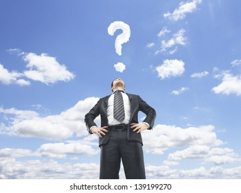 businessman standing and looking up in sky