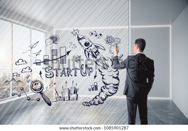 Businessman standing in modern interior with creative business sketch. Leadership, success and strategy concept.