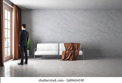 Businessman standing in modern living room with sofa and blank concrete wall. Art and design concept.