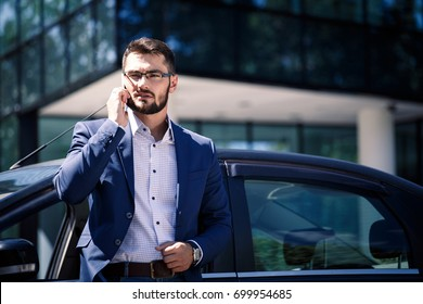 Businessman standing near the car. Office building on the background