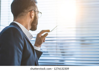 The businessman standing near the window with jalousie