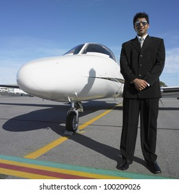 Businessman standing next to nose of airplane