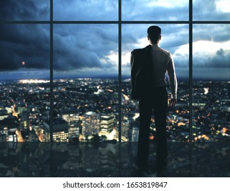 Businessman standing in night office and looking to megapolis city view. Occupation and worker concept.