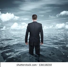 businessman standing in ocean and cloud