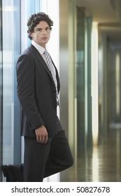 Businessman standing in office corridor, portrait