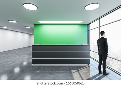 Businessman standing in office lobby hall with reception desk and copy space on green wall. Mock up,