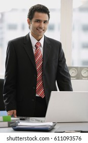 Businessman standing in office, looking at camera