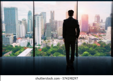 Businessman standing  in a office and looking at city
