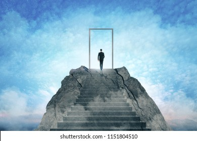 Businessman standing on abstract mountain with door on sky background. Promotion and dream concept