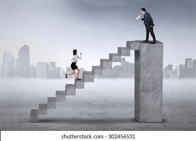 Businessman standing on the bar and calling his colleague to run faster on the stair
