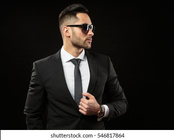 Businessman standing on black background. handsome Man in suit