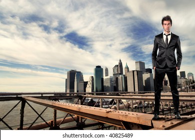 businessman standing on a bridge and manhattan on the background