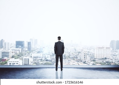 Businessman standing on building. City background with copy space. Success and vision concept