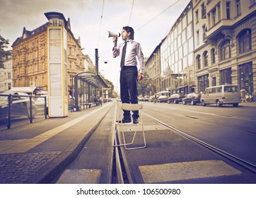 Businessman standing on a chair and screaming into a megaphone in the middle of a city street