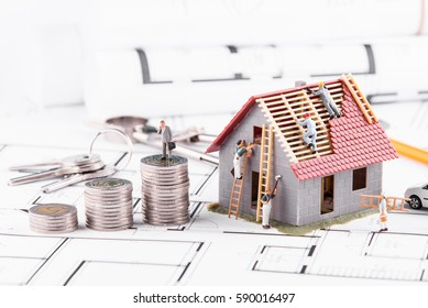 Businessman standing on coins next to the cottage. The concept of earning and spending money.