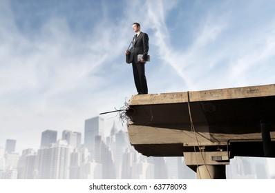 Businessman standing on the edge of a bridge