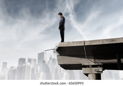 Businessman standing on the edge of a broken bridge and looking into the void