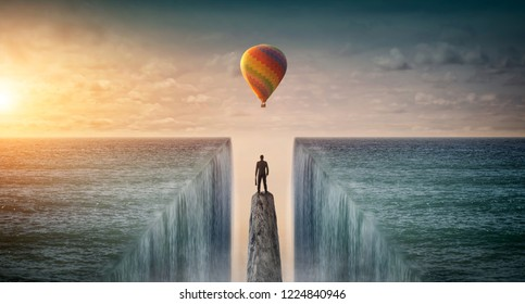 Businessman standing on edge of rock mountain and looking at Balloon. Concept for success