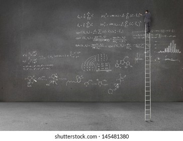 Businessman standing on a giant ladder and writing maths equations on a grey wall