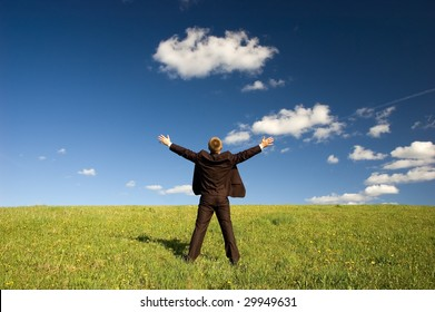Businessman standing on green grass - arms outstretched, deep blou sky and white clouds