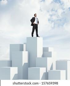Businessman standing on highest cube