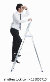 Businessman standing on a ladder