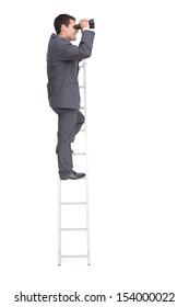 Businessman standing on ladder using binoculars against white background