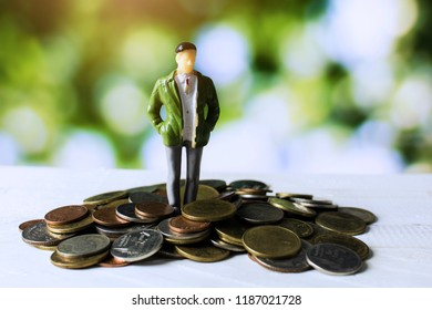 businessman standing on money coins, business people or investor looking on money pile with vision of goal and target