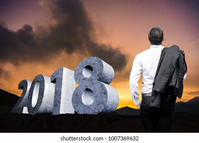 Businessman Standing on mountains at Sunset with concrete text 2018 idea market plan in new year
