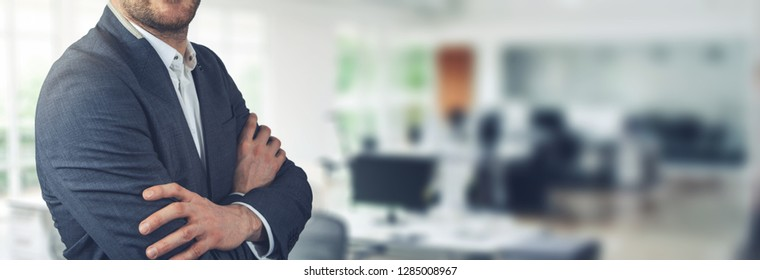 businessman standing on office background with arms crossed. copy space