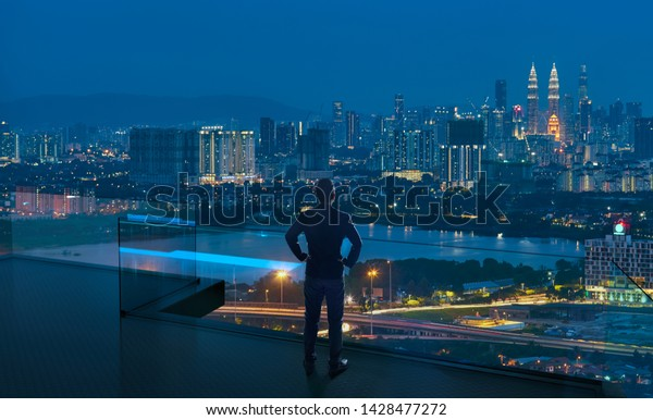 Businessman standing on open roof top balcony watching city night view . Business ambition and vision concept .