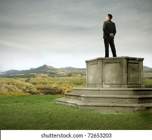 Businessman standing on a pedestal on a green meadow