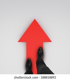 businessman standing on red arrow o a white background
